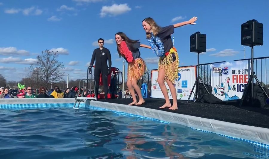 Emery Brown 23 and Lucy Chiozza 23 jump into the freezing water at the Polar Bear Plunge.
